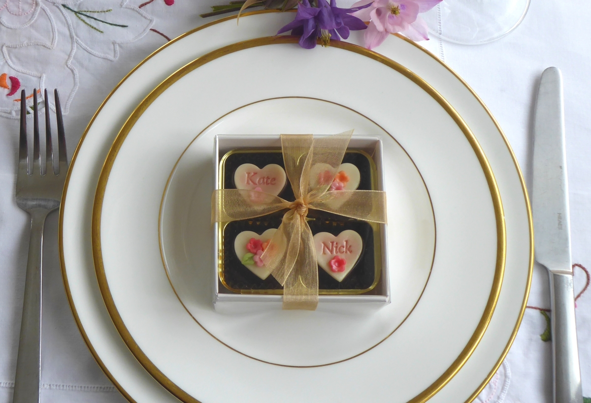 A box of four, transparent lid tied with gold organza ribbon